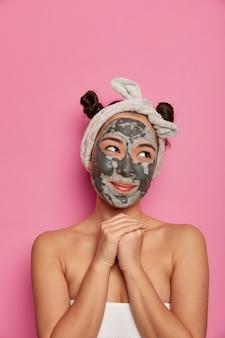Junge frau trägt natürliche gesichtsmaske der hautmaskenbehandlung nach dem baden