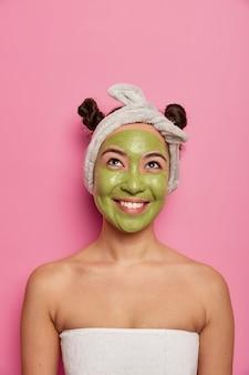 Junge frau trägt natürliche gesichtsmasken-hautbehandlungen nach dem baden