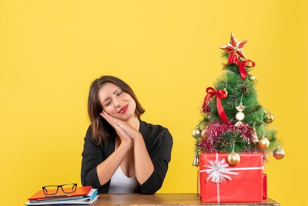 Junge frau träumt von etwas, das an einem tisch nahe geschmücktem weihnachtsbaum im büro auf gelb sitzt