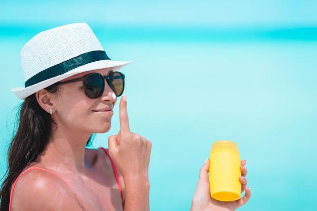 Junge frau tragen creme auf ihre nase am strand auf