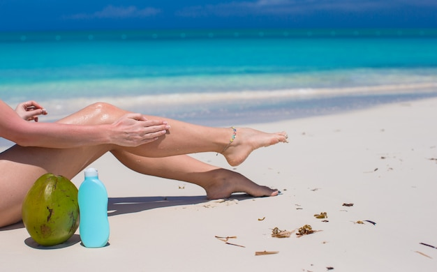 Junge frau tragen creme auf ihren glatten gebräunten beinen am tropischen strand auf