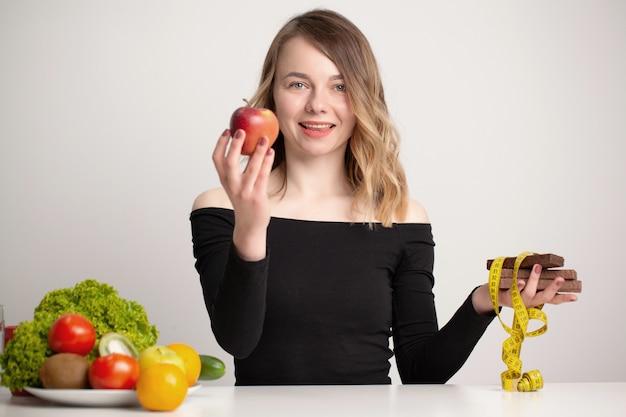 Junge frau trifft eine wahl zwischen gesundem und ungesundem essen.