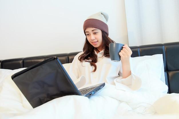 Junge frau trinkt kaffee bei der verwendung von laptop im bett zu hause