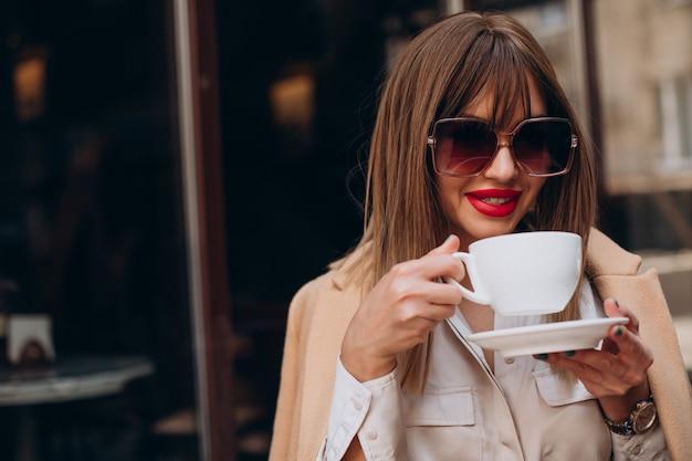 Junge frau trinkt kaffee in einem café auf der terrasse