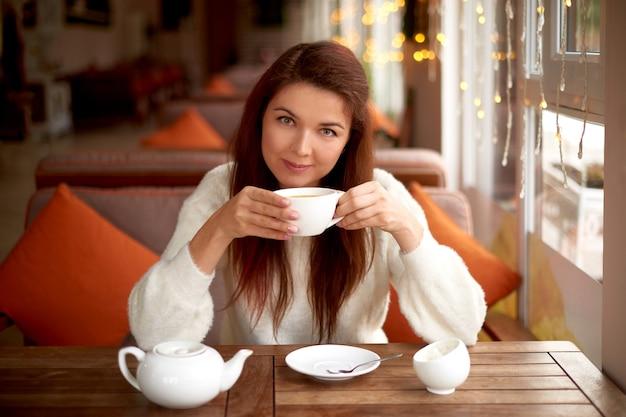 Junge frau trinkt tee im café. tischset für tee mit weißem wasserkocher, zuckerdose und tasse. morgens