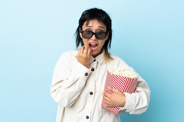 Junge frau über blauer wand mit 3d brille und hält einen großen eimer popcorn