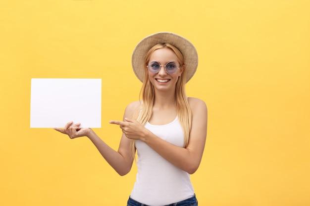 Junge frau über dem gelben hintergrund, der blatt des leeren papiers hält