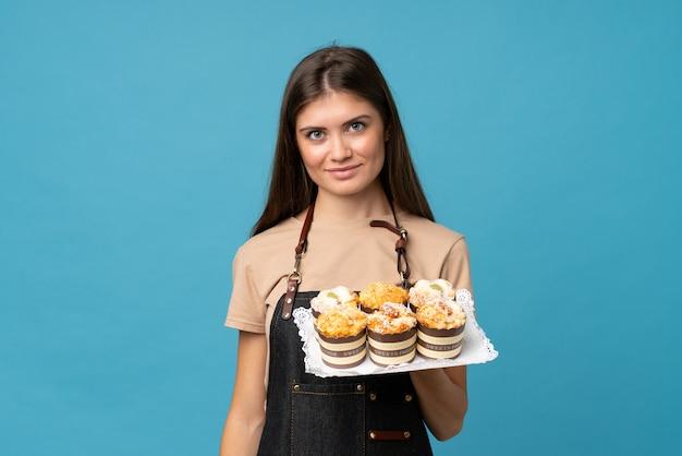 Junge frau über dem lokalisierten blau, das minikuchen hält