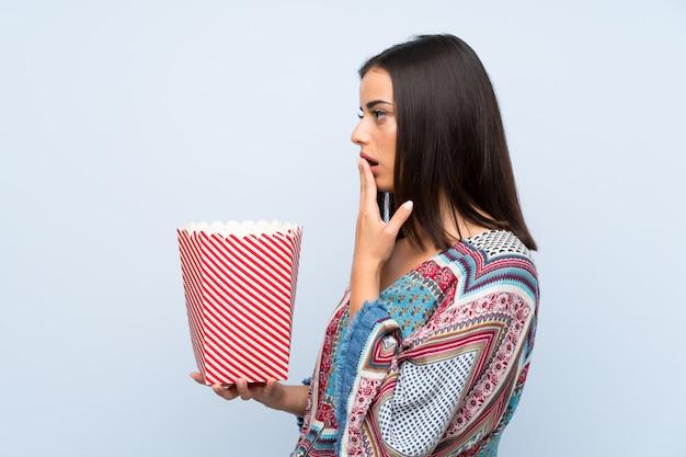 Junge frau über der lokalisierten blauen wand, die eine schüssel popcorn hält