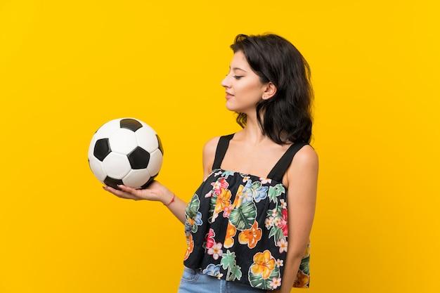 Junge frau über der lokalisierten gelben wand, die einen fußball hält