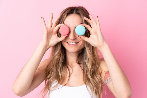 Junge frau über der lokalisierten rosa wand, die bunte französische macarons als gläser trägt