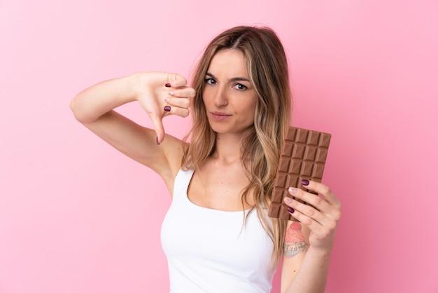 Junge frau über der lokalisierten rosa wand, die eine schokoladentablette macht schlechtes signal nimmt