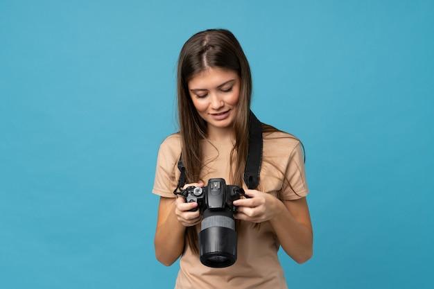 Junge frau über getrenntem blau mit einer berufskamera