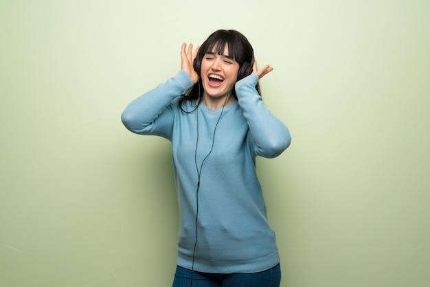 Junge frau über grüner wand hörend musik mit kopfhörern