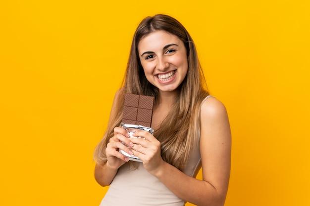 Junge frau über isolierte gelbe wand, die eine schokoladentafel nimmt und glücklich