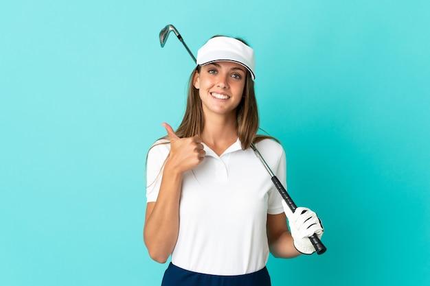 Junge frau über isoliertem blauem hintergrund beim golfspielen und mit daumen nach oben, weil etwas gutes passiert ist