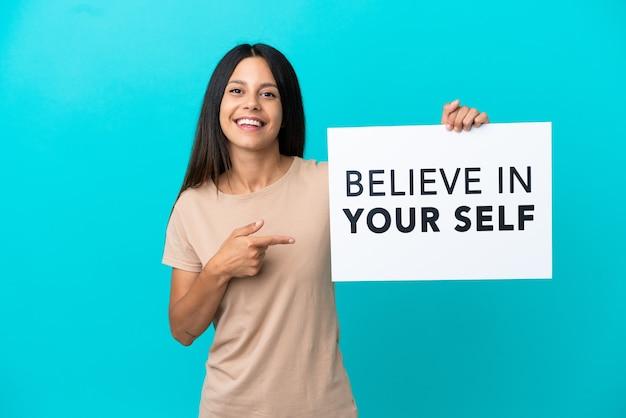 Junge frau über isoliertem hintergrund, die ein plakat mit dem text believe in your self hält und darauf zeigt