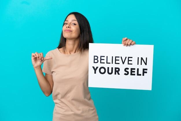 Junge frau über isoliertem hintergrund, die ein plakat mit dem text believe in your self mit stolzer geste hält