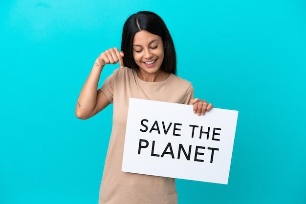 Junge frau über isoliertem hintergrund, die ein plakat mit dem text save the planet hält und darauf zeigt