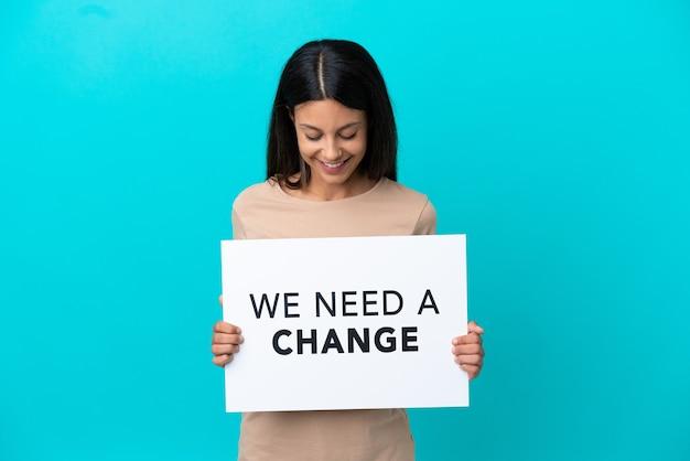 Junge frau über isoliertem hintergrund, die ein plakat mit dem text we need a change hält
