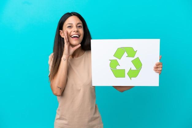 Junge frau über isoliertem hintergrund, die ein plakat mit recycling-symbol hält und schreit