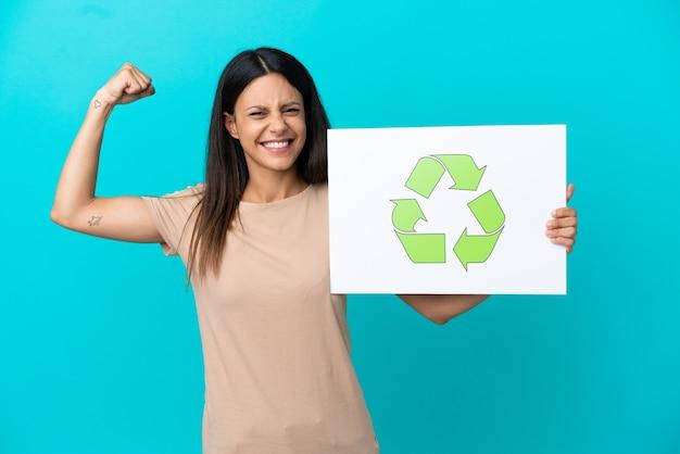 Junge frau über isoliertem hintergrund, die ein plakat mit recycling-symbol hält und starke geste macht