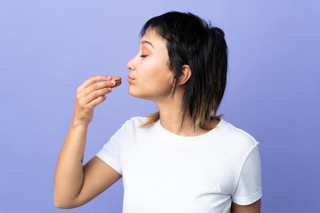Junge frau über isoliertem purpur, das bunte französische macarons hält und es isst