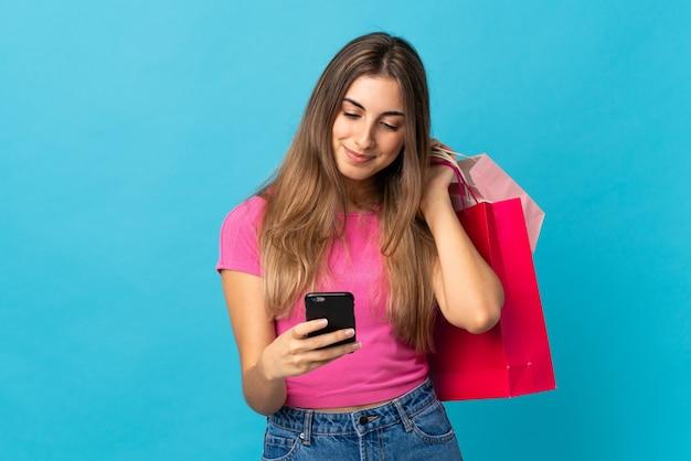 Junge frau über isolierter blauer wand, die einkaufstaschen hält und eine nachricht mit ihrem handy an einen freund schreibt