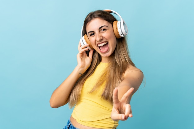 Junge frau über isolierter blauer wand, die musik hört und singt