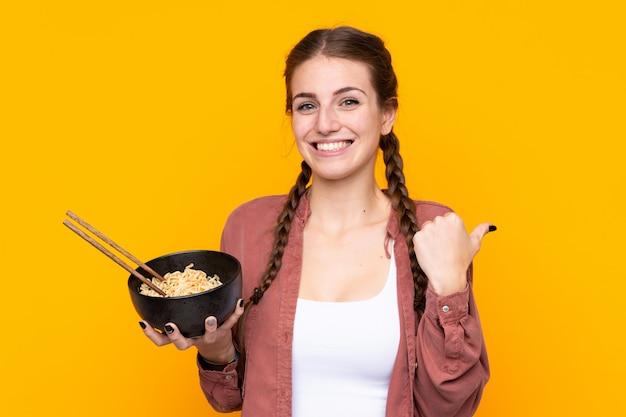 Junge frau über isolierter gelber wand, die zur seite zeigt, um ein produkt zu präsentieren, während eine schüssel nudeln mit stäbchen hält
