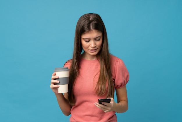 Junge frau über lokalisiertem blauem haltenem kaffee zum mitnehmen und einem mobile