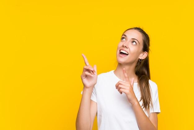 Junge frau über lokalisiertem gelbem hintergrund zeigend mit dem zeigefinger eine großartige idee