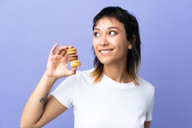 Junge frau über lokalisiertem purpur, der bunte französische macarons hält und beim lächeln nach oben schaut