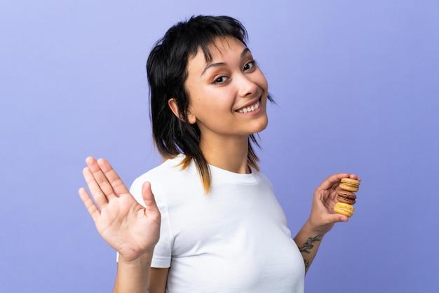 Junge frau über lokalisiertem purpur, der bunte französische macarons hält und salutiert