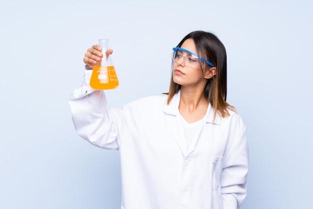 Junge frau über lokalisierter blauer wand mit einem wissenschaftlichen reagenzglas