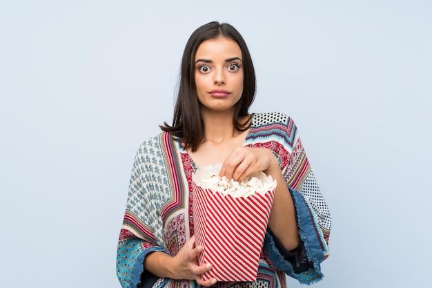 Junge frau über lokalisierter blauer wand popcorn essend