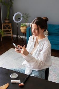 Junge frau überprüft ihren vlog auf einem smartphone