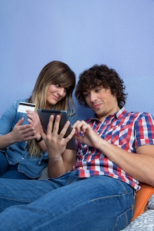 Junge frau überzeugt ihren mann, einen online-einkauf mit kreditkarte zu tätigen