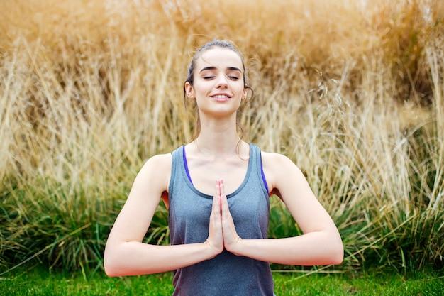 Junge frau übt yoga und meditiert im lotussitz im park