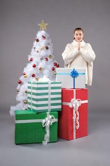 Junge frau um weihnachtsgeschenke auf grau