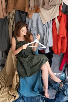 Junge frau, umgeben von kleiderhaufen