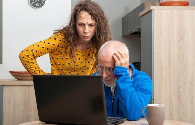 Junge frau und älterer mann haben problem mit laptop-computer