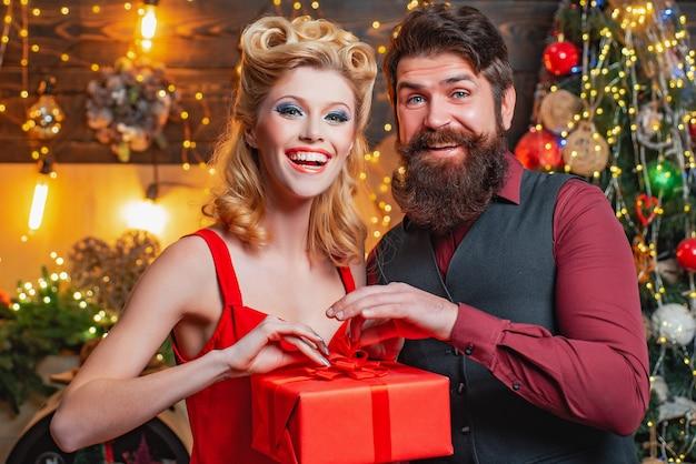 Junge frau und bärtiger mann in der weihnachtskleidung auf weihnachtsbaumhintergrund