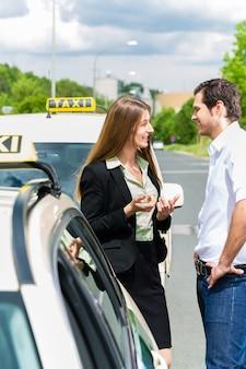 Junge frau und fahrer stehen zusammen vor dem taxi, sie hat ihr ziel erreicht