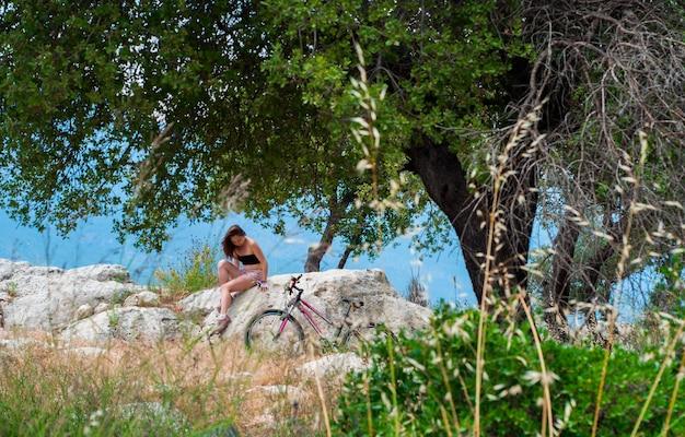 Junge frau und fahrrad auf felsigem
