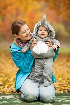 Junge frau und ihr baby im kostüm gekleidet