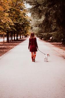 Junge frau und ihr jack russell-hund, die in einen park gehen