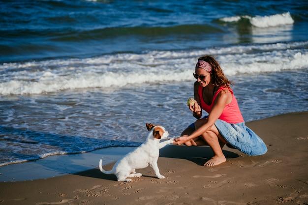 Junge frau und ihr netter kleiner jack russell-terrier, die am strand spielt