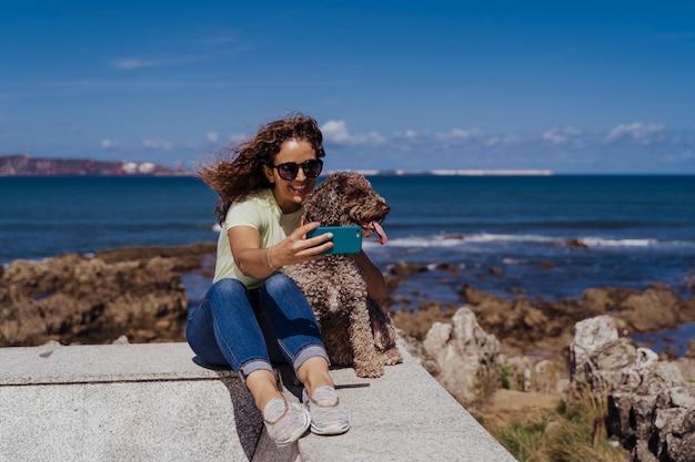 Junge frau und ihr netter spanischer wasserhund, die draußen zusammen an einem sonnigen und windigen tag genießen. frau, die selfie mit handy nimmt.