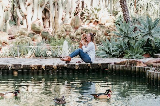 Junge frau und ihr niedlicher welpe des cockerspaniels draußen in einem park mit einem see